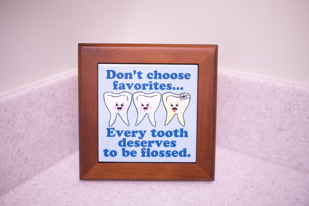 """Framed graphic says """"Don't choose favorites... every tooth deserves to be flossed."""""""