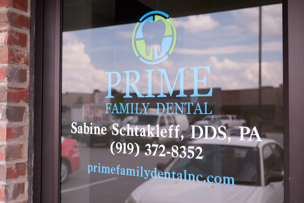 Glass door to the Prime Family Dental office. The clouds and parking lot are reflected in the glass.