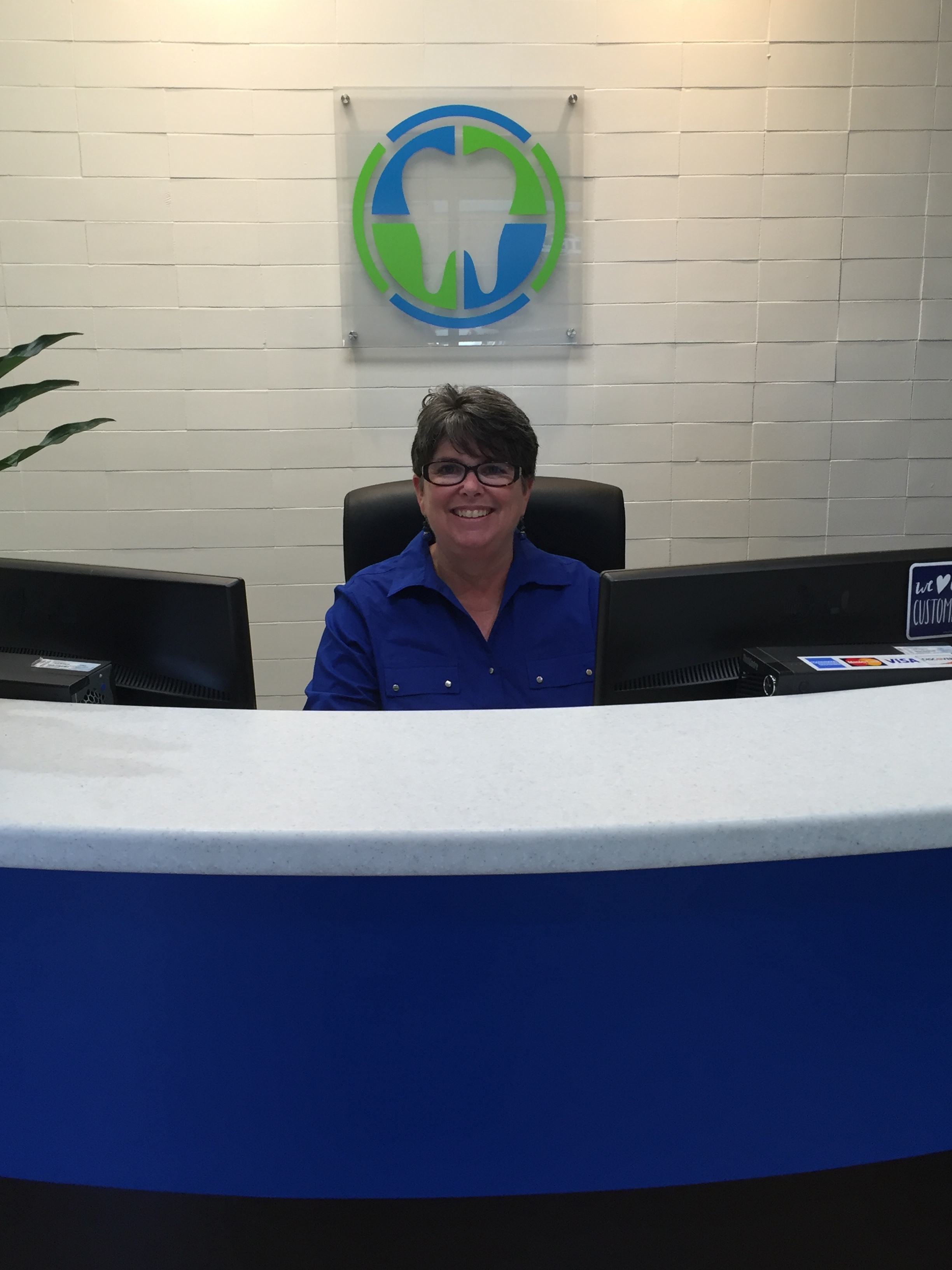 Lynn sits behind a desk, smiling, in front of the Prime Family Dental logo.