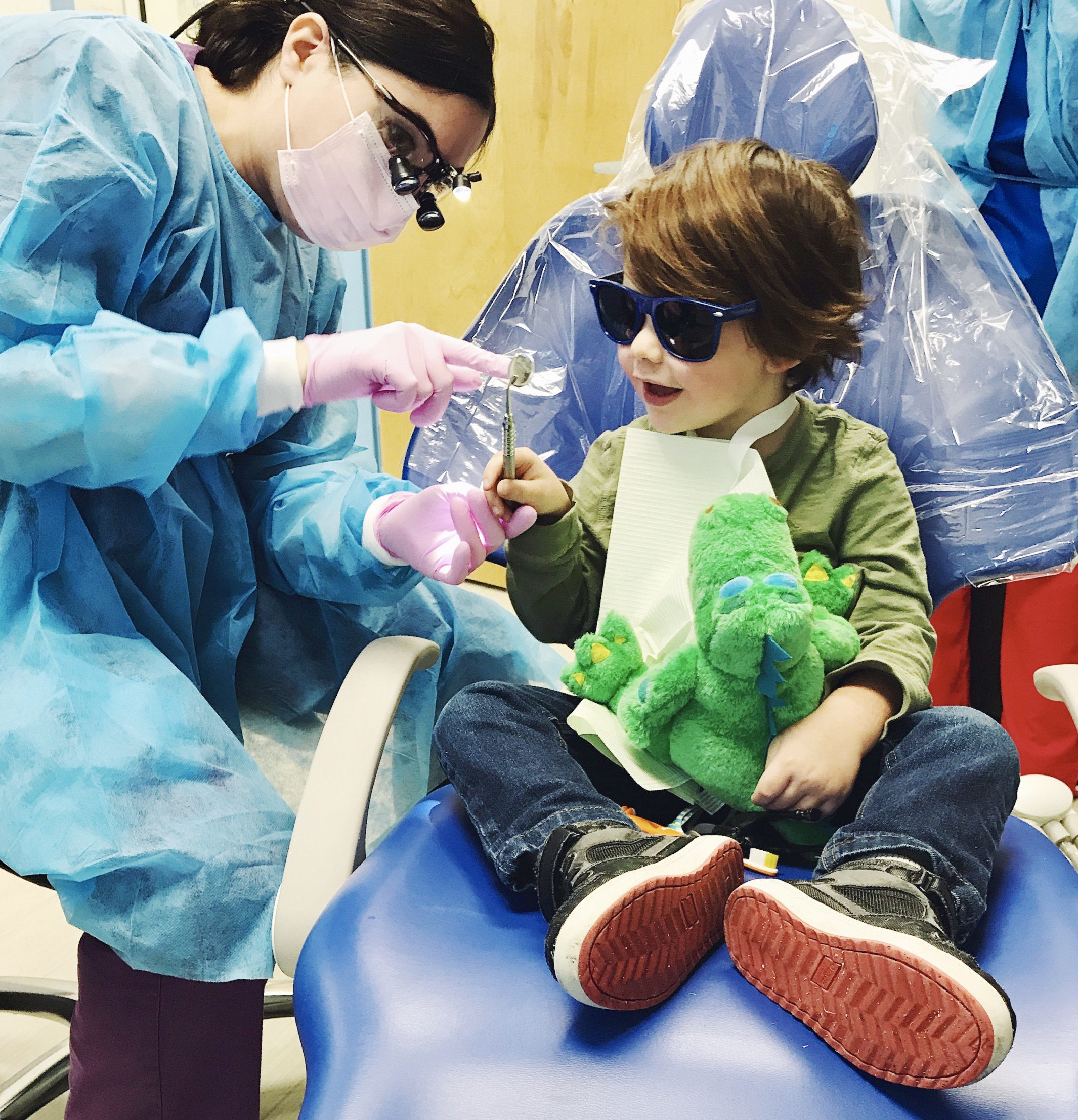 A young boy sits on a blue dental chair, wearing sunglasses and holding a stuffed alligator. He is smiling as Dr. Schtakleff shows him an instrument that she is using.