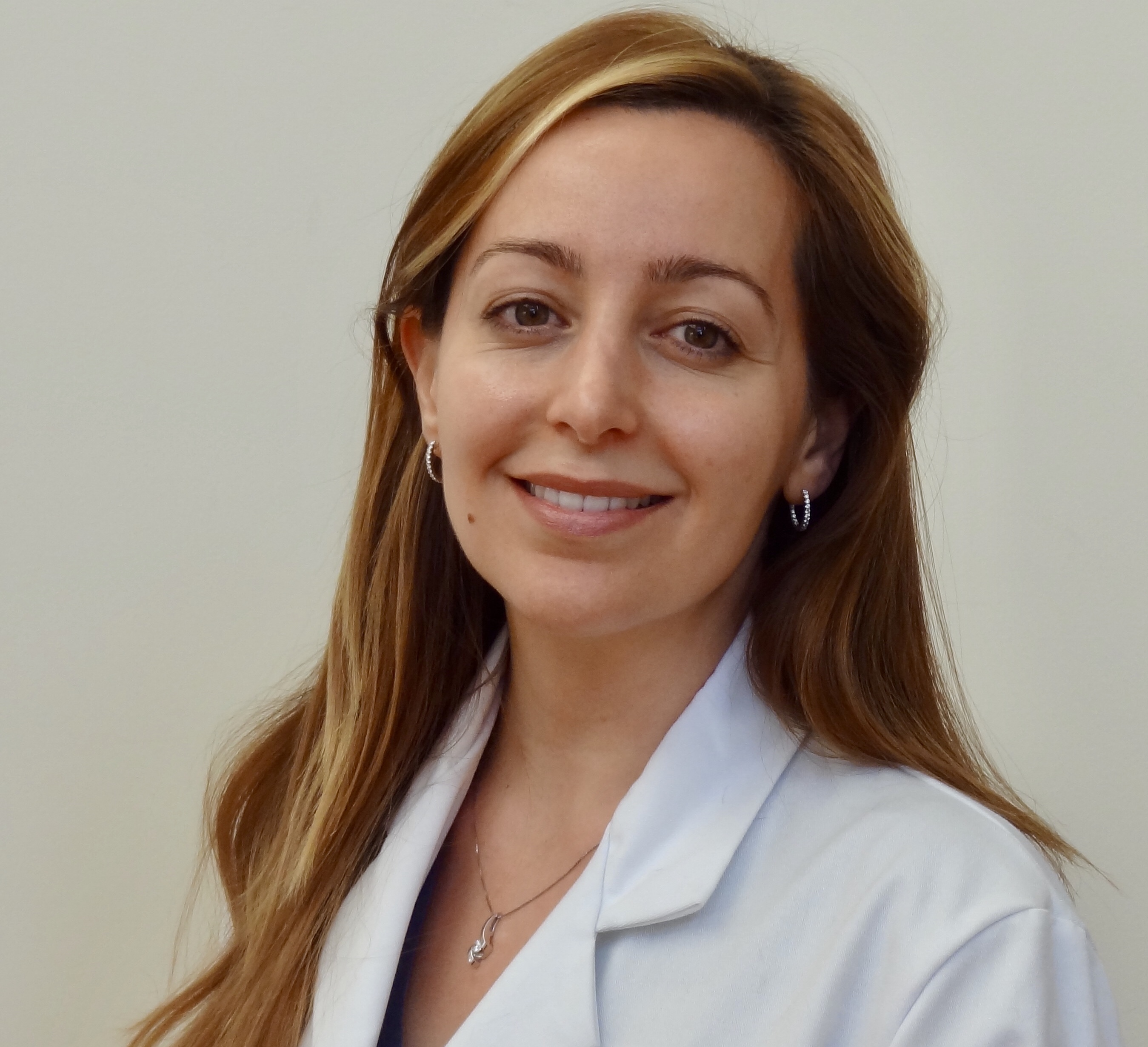 Dr. Verga smiling in a white lab coat.